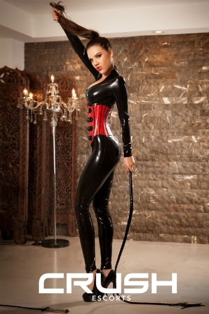 Erika is wearing a black and red latex outfit and high heeled shoes.