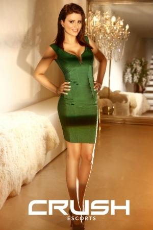 Estella wearing a green dress.