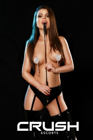 Rosalyn in latex black underwear and kissing a whip.