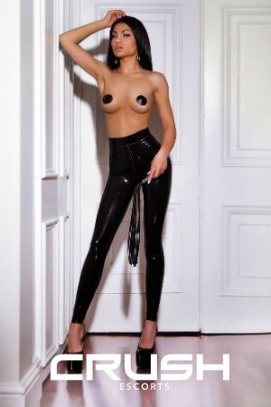 Miki in black latex pants and black high heels.