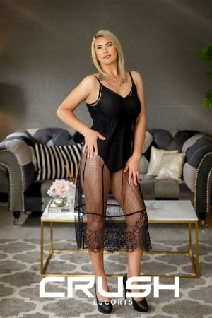 Mirage is posing in a black lace dress and high heels.
