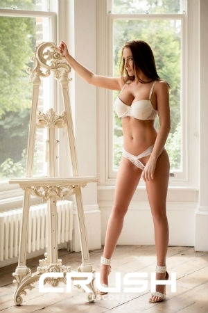Shanon is wearing white lingerie and high heels.