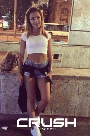Ilinca wearing a white t shirt and short blue jeans.