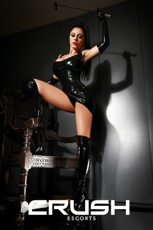 Emely posing in a latex outfit.