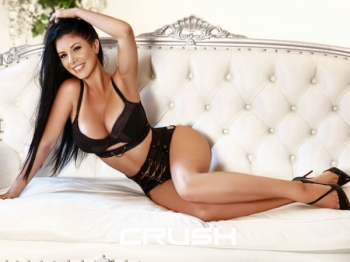 Emely is laying on the couch in black lingerie.