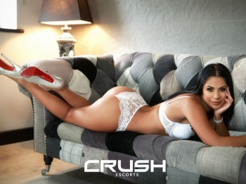 Dinora is laying on the couch wearing white lingerie.