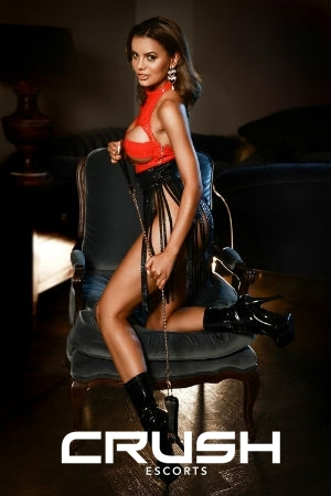 Chrisma is wearing a black and red latex outfit and high heels.