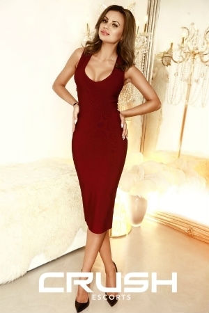 Chrisma is wearing a dark red dress and high heels.
