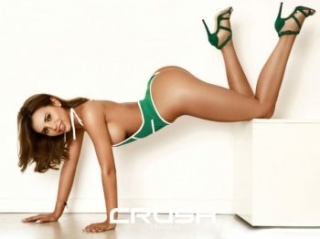 Chrisma is posing sexy in a green body and heels.