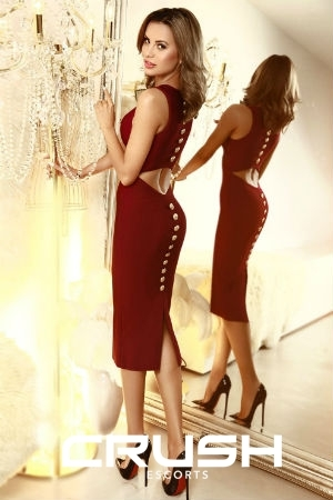 Chrisma is wearing a dark red dress and heels.