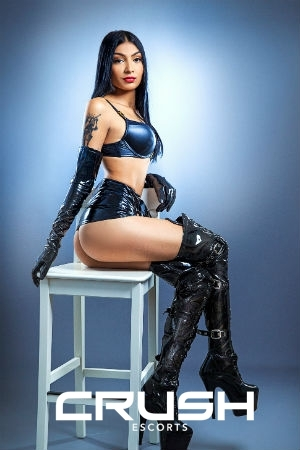 Eliff is posing in a latex outfit and boots.