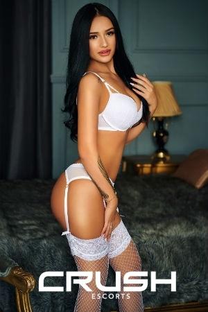 Xandra is posing in white lingerie.
