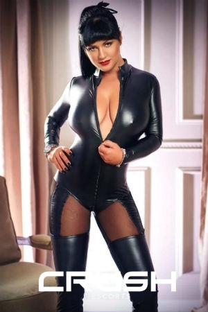 Devona is posing in a black latex outfit.