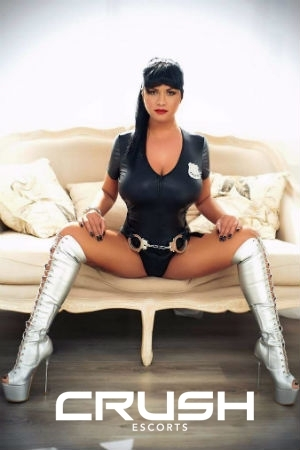 Devona is sitting on a couch in a latex outfit and silver boots.