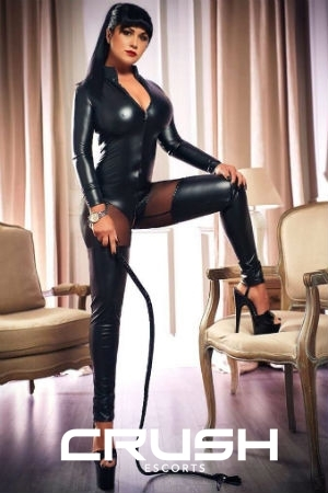 Devona is posing in a latex outfit and holding a whip.