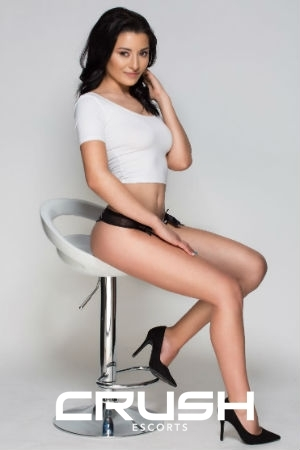 Olya is posing on a chair wearing a white top and black underwear.