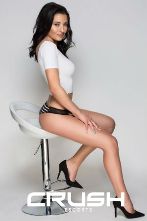 Olya is posing on a chair in a white top, black underwear and high heels.