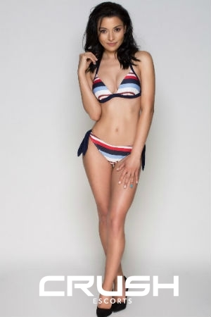 Olya is wearing a white, blue and red swimsuit.