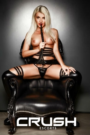 Renata is topless and wearing a black BDSM outfit and latex boots.