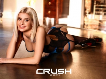 Cezy is posing on the floor in a black and blue lace body.