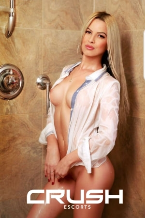 Maly is posing in the shower in a wet shirt.