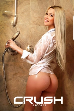 Maly is posing in the shower in a wet white shirt.