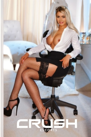 Andra is posing sexy on a chair wearing a secretary outfit and high heels.