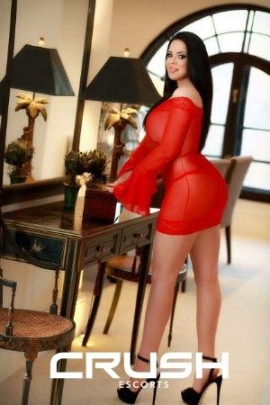 Debie is posing in a red dress and high heels.