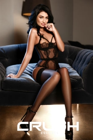 Francesca is posing on the couch in a black lace corset and stockings.