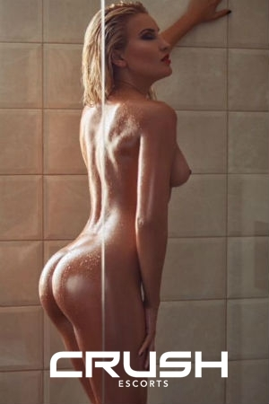 Nataly is posing naked in the shower.