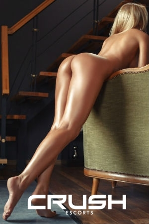 Nataly is posing naked on a chair.