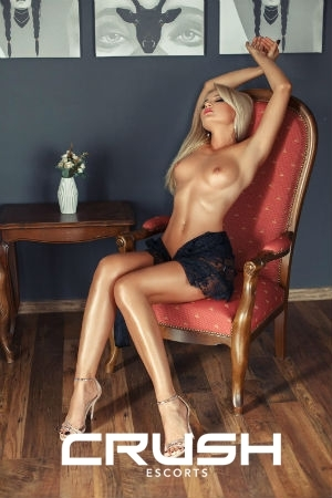 Nataly is sitting on a chair topless and wearing a black lace skirt.