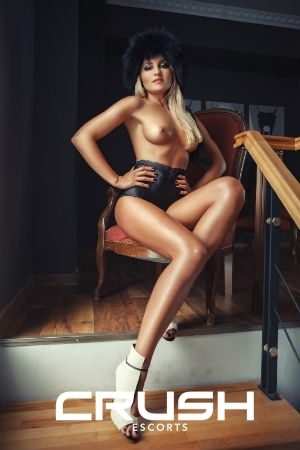 Nataly is sitting on a chair topless and wearing black underwear and high heels.