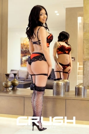 Luna is wearing red and black lingerie, stockings and heels.