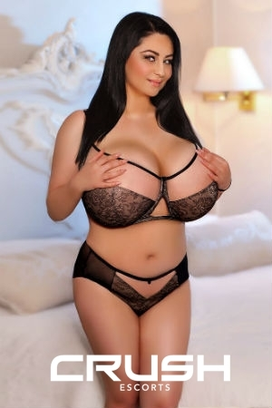Busty Poly is posing in black and beige lingerie.