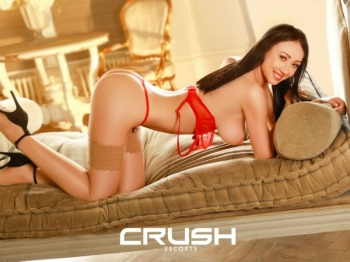 Charlote is posing on the bed wearing red lingerie and stockings.