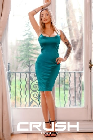 Sloane from Crush Escorts is wearing a green sexy dress and black heels.