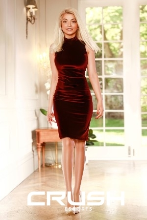 Raisa from Crush escorts is wearing a red velvet dress and beige heels.