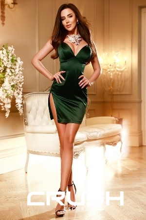 Isabel London escort is wearing a green sexy dress and high heels.