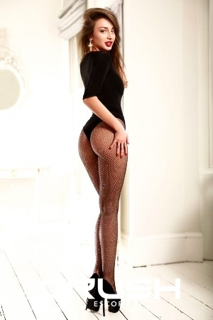 Anca London escort is posing in a black body, stockings and high heels.
