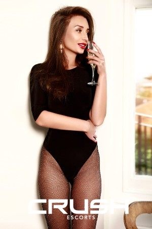 Anca London escort is wearing a black body, stockings and holding a champagne glass.