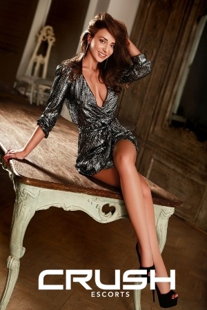 Anca is posing sexy on a table wearing an elegant dress.