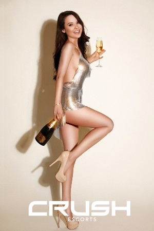 Karolina London escort looking stunning in a silver dress, high heels and holding a champagne bottle
