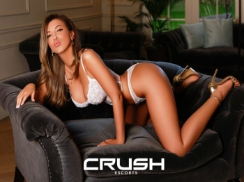 Blaise is posing on a couch wearing white lingerie.